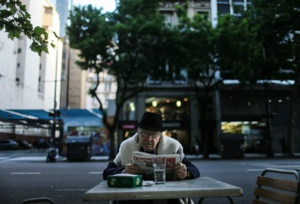 Homem lê jornal em uma cafeteria em Buenos Aires, na Argentina, em 20 de novembro de 2015 (Mario Tama/Getty Images)