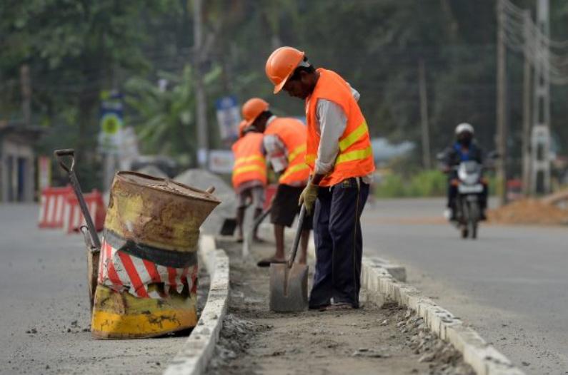 """Operários da construção civil do Sri Lanka trabalham em uma estrada em Colombo, em 5 de agosto de 2018. O banco central do Sri Lanka anunciou em 3 de agosto que havia obtido um empréstimo da China de um bilhão de dólares, já que a ilha, um elo chave da ambiciosa iniciativa de Pequim, """"Um Cinturão, Um Caminho"""", estreitou seu relacionamento com os chineses (Lakruwan Wanniarachchi/AFP/Getty Images)"""