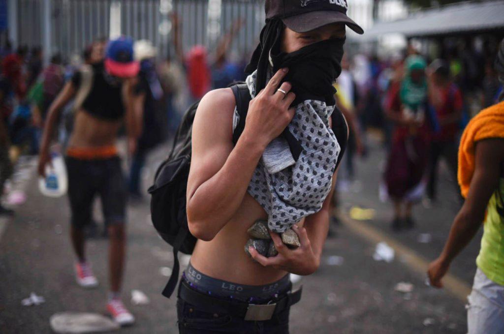 Migrante hondurenho que acompanha uma caravana com destino aos EUA é fotografado segurando pedras na fronteira entre Ciudad Tecun Uman, na Guatemala, e Ciudad Hidalgo, no México, em 28 de outubro de 2018 (Santiago Billy/AFP/Getty Images)