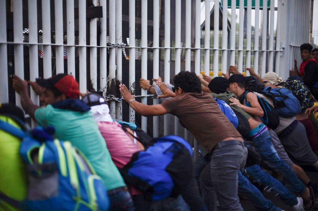 Migrantes hondurenhos que seguem em caravana rumo aos EUA derrubam portão na fronteira entre Ciudad Tecun Uman, na Guatemala, e Ciudad Hidalgo, no México, em 28 de outubro de 2018 (Santiago Billy/AFP/Getty Images)