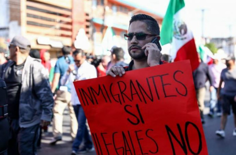 """Rodrigo Morgoza, morador de Tijuana, segura uma placa que diz """"migrantes sim, ilegais não"""" durante um protesto contra a caravana de migrantes da América Central em Tijuana, México, em 18 de novembro de 2018 (Charlotte Cuthbertson/Epoch Times)"""