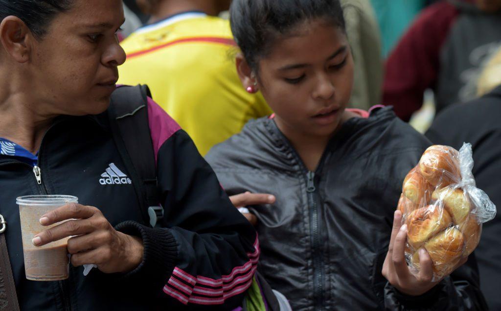 Migrantes venezuelanos recebem lanches doados em um acampamento improvisado perto de um terminal de ônibus em Bogotá, em 11 de setembro de 2018 (Raul Arboleda/AFP/Getty Images)