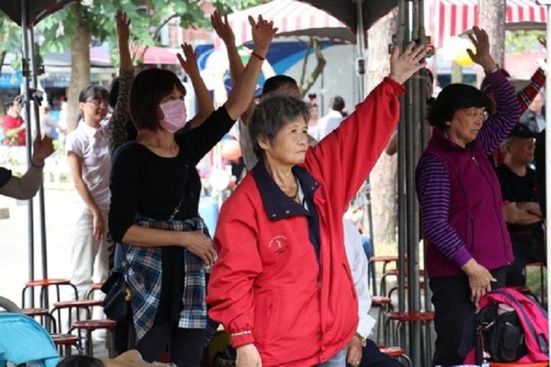 Membros da audiência na demonstração do exercício do Falun Gong copiam os movimentos do exercício (Minghui.org)