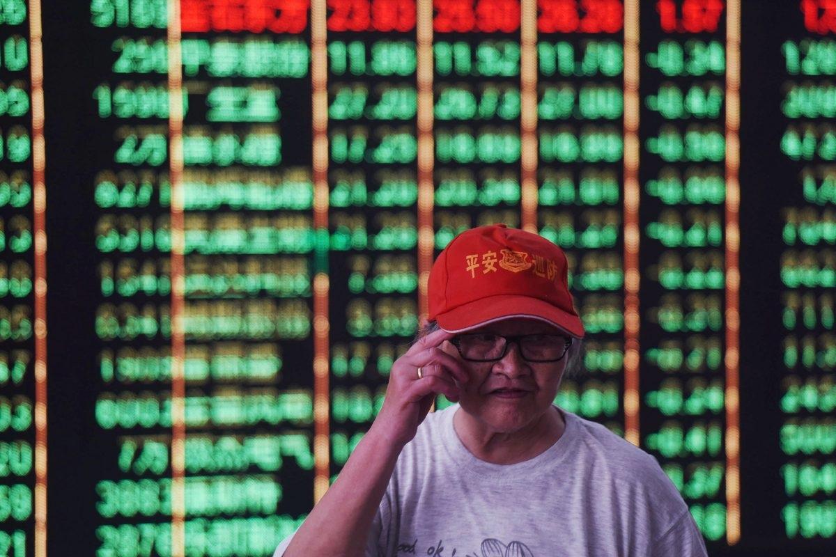 Chinesa em frente a uma tela que mostra os números do mercado de ações de uma empresa de valores mobiliários em Hangzhou, na província chinesa de Zhejiang, em 19 de junho de 2018 (AFP/Getty Images)