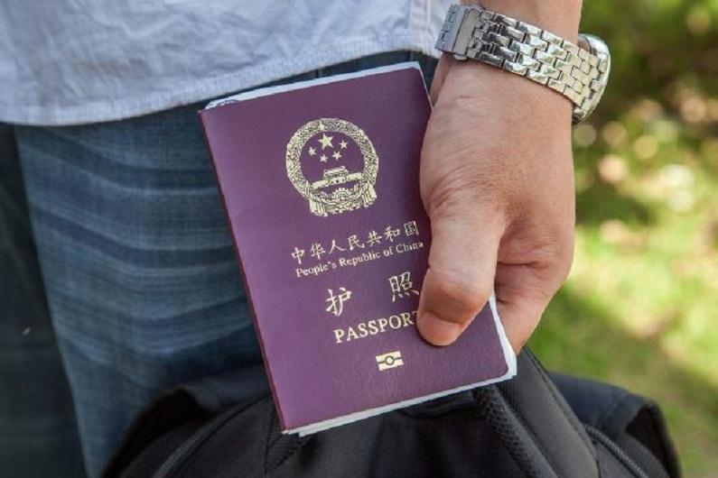 Cidadão chinês segura seu passaporte (Omar Havana/Getty Images)