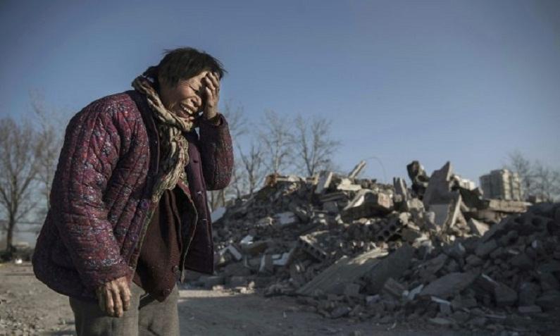 Zheng Yuzhi, cuja casa foi demolida pelas autoridades há três meses e que agora está desabrigada, se desespera ao ver a destruição de uma área que já esteve repleta de casas para trabalhadores migrantes, no distrito de Changing em Pequim, na China, em 5 de dezembro de 2017 (Kevin Frayer/Getty Images)