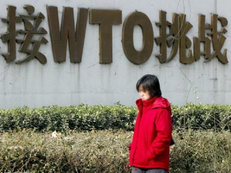 Chinesa passa por um letreiro que proclama a participação da China na Organização Mundial do Comércio (OMC) (Goh Chai Hin/AFP/Getty Images)