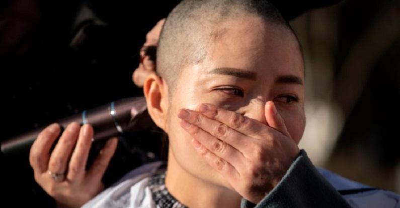 Li Wenzu raspa a cabeça em protesto contra a prisão de seu marido, o advogado chinês de direitos humanos Wang Quanzhang, preso durante a Operação 709 em Pequim, em 17 de dezembro de 2018 (Fred Dufour/AFP/Getty Images )