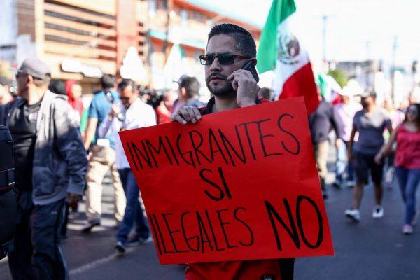 """Rodrigo Morgoza, morador de Tijuana, segura um cartaz que diz """"Imigrantes sim, ilegais não"""" durante um protesto contra a caravana de migrantes da América Central em Tijuana, México, em 18 de novembro de 2018 (Charlotte Cuthbertson/Epoch Times)"""