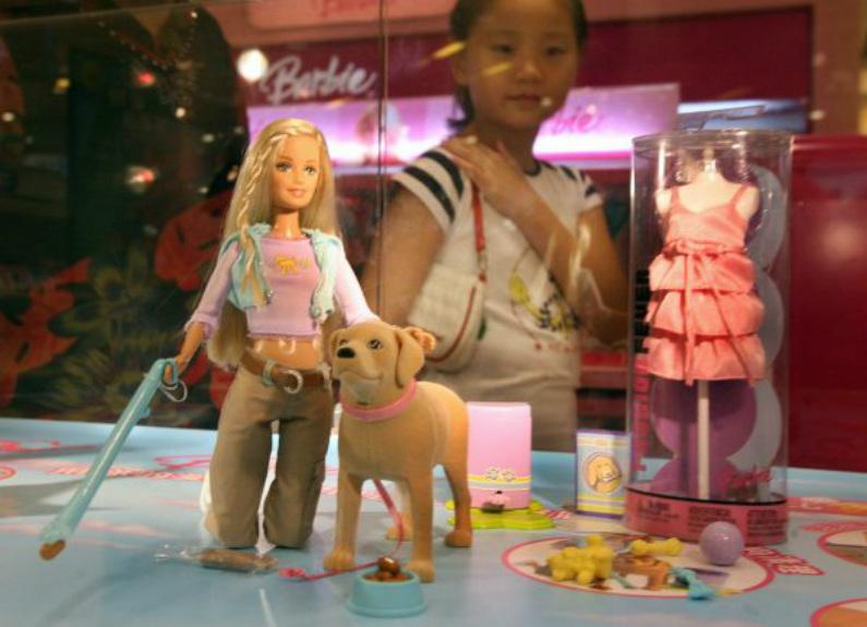 """Menina chinesa olha para uma boneca """"Barbie and Tanner"""", feita pela gigante norte- americana de brinquedos Mattel, que ainda está à venda na China apesar de ter sido retirada do mercado nos Estados Unidos, em uma loja em Xangai, no dia 15 de agosto de 2007. Segundo a comissão, o acessório """"pá"""" que vem com a boneca tem um pequeno ímã que pode facilmente soltar-se (Mark Ralston/AFP/Getty Images)"""