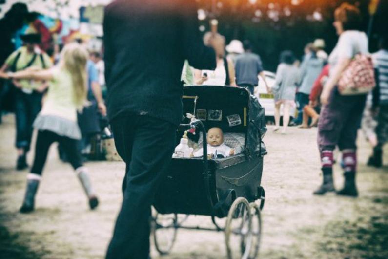 Homem caminha empurrando um carrinho de bebê pela rua com uma boneca dentro (Rachel Docherty/Flickr/CC BY 2.0)