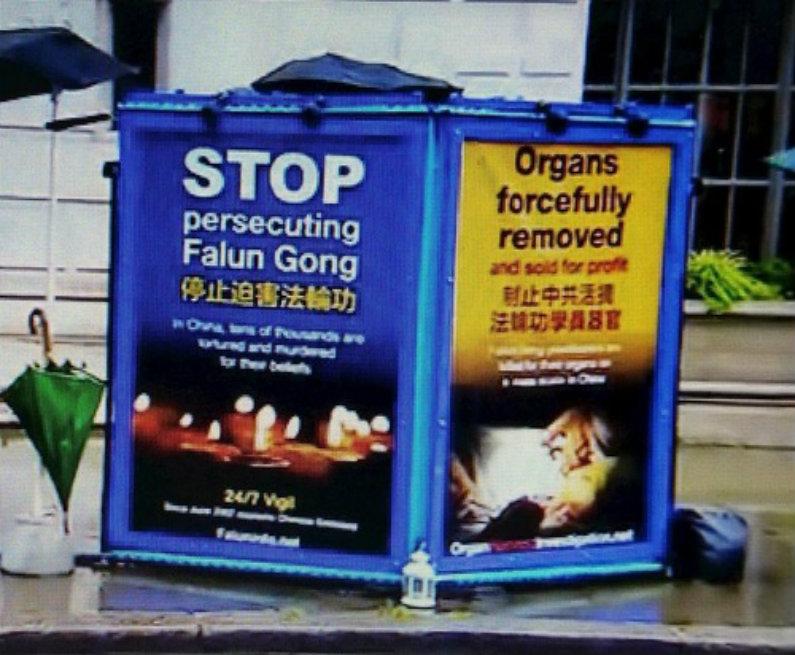Cartazes de praticantes do Falun Gong realizando um protesto pacífico em frente à embaixada da China em Londres