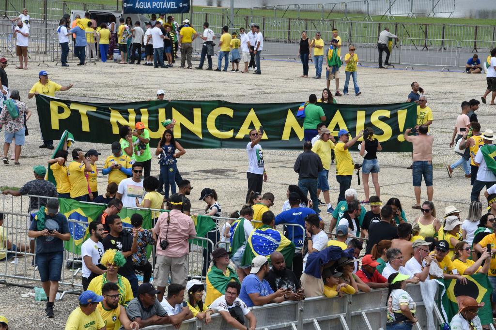 """Apoiadores do presidente Jair Bolsonaro seguram uma faixa que diz """"PT (Partido dos Trabalhadores) nunca mais"""", antes da cerimônia de posse de Bolsonaro na praça dos Três Poderes, em frente ao Palácio do Planalto, Brasília, em 1º de janeiro de 2019 (EVARISTO SA / AFP / Getty Images)"""