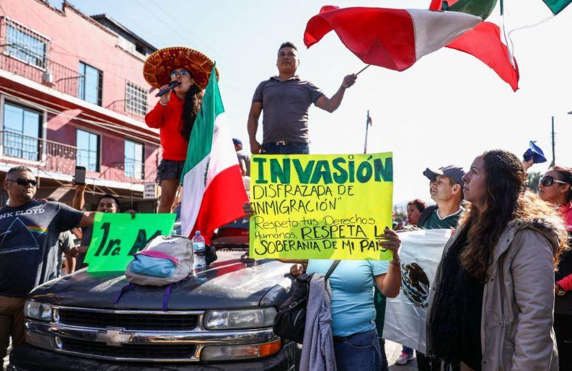 Mexicanos protestam contra a caravana de migrantes vinda da América Central, enquanto o batalhão de choque os mantém longe do campo de imigrantes em Tijuana, México, em 18 de novembro de 2018 (Charlotte Cuthbertson / Epoch Times)