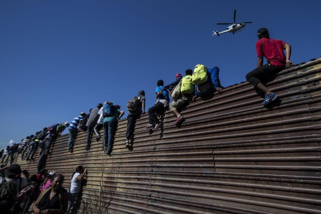 Grupo de migrantes da América Central, principalmente hondurenhos, escala uma barreira de metal na fronteira entre o México e os Estados Unidos, perto da fronteira com El Chaparral, em Tijuana, Estado de Baja California, México, em 25 de novembro de 2018 (PEDRO PARDO / AFP / Getty Images)