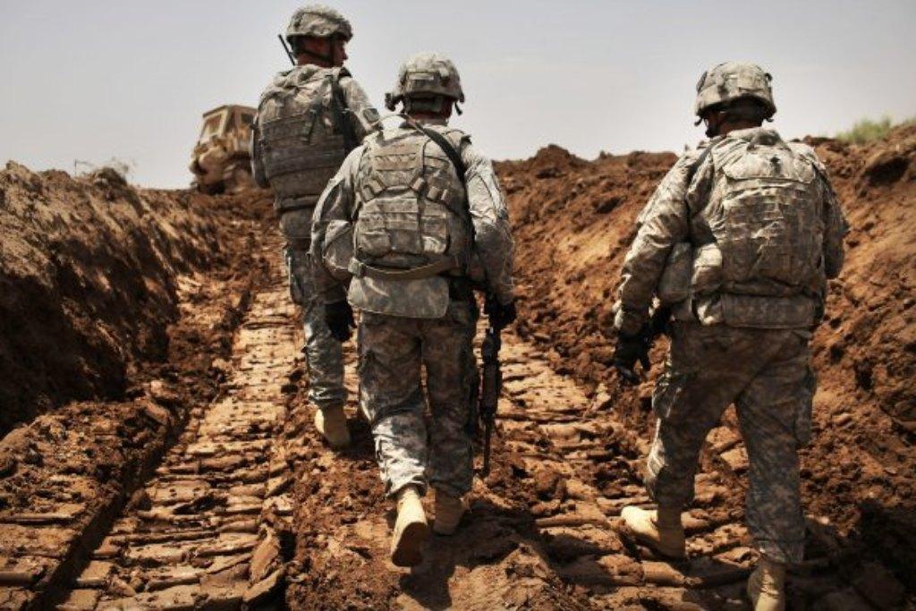 Soldados norte-americanos do 3º Regimento de Cavalaria Blindada patrulham uma nova vala escavada para proteger a base de ataques em Iskandariya, província de Babil, no Iraque, em 19 de julho de 2011 (Spencer Platt / Getty Images)