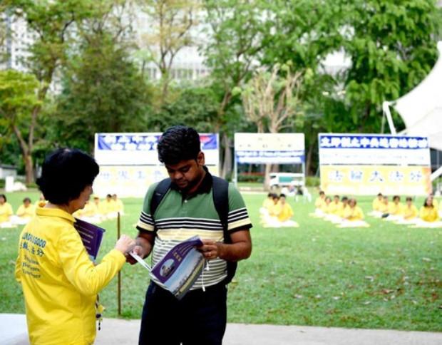 Turistas e moradores locais pararam para conversar com os praticantes. Alguns leram os expositores, enquanto outros tiraram fotos e filmaram o evento (Minghui.org)