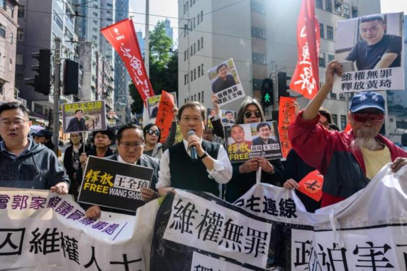 """Ativistas pró-democracia em Hong Kong fazem caminhada durante manifestação em apoio aos detidos, o advogado chinês de direitos humanos Wang Quanzhang, e o primeiro """"ciber-dissidente"""" da China e fundador do site de direitos humanos """"64 Tianwang"""", Huang Qi, em Hong Kong, em 29 de janeiro de 2019 (ANTHONY WALLACE / AFP / Getty Images)"""