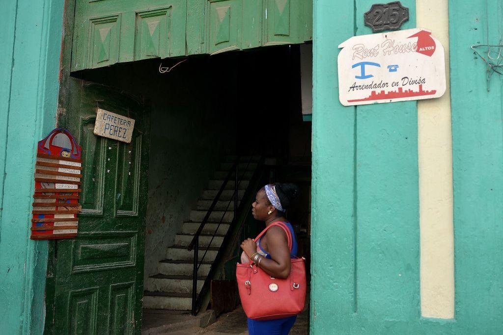 Mulher se detém na porta de uma casa com uma placa anunciando uma cafeteria do chamado setor privado ou cuentapropista em Havana, em 10 de junho de 2018 (YAMIL LAGE / AFP / Getty Images)