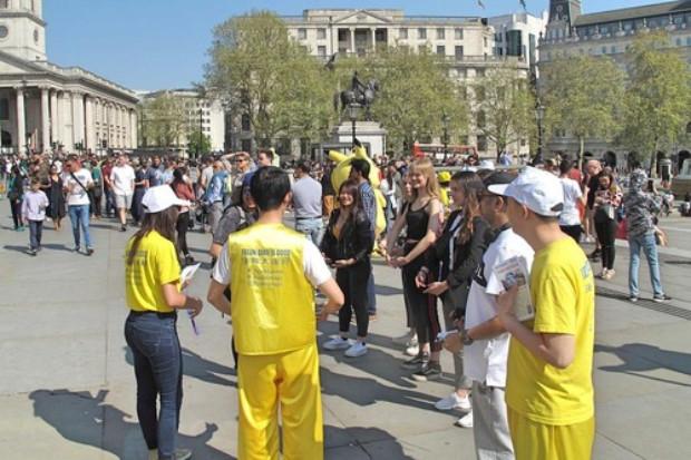 Turistas conversam com praticantes e aprendem sobre o Falun Gong (Minghui.org)