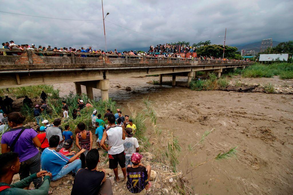 Venezuelanos cruzam a ponte internacional bloqueada Simón Bolívar em Cúcuta, na Colômbia, na fronteira com a Venezuela, enquanto outros observam das margens do rio Táchira, em 2 de abril de 2019 (SCHNEYDER MENDOZA / AFP / Getty Images)