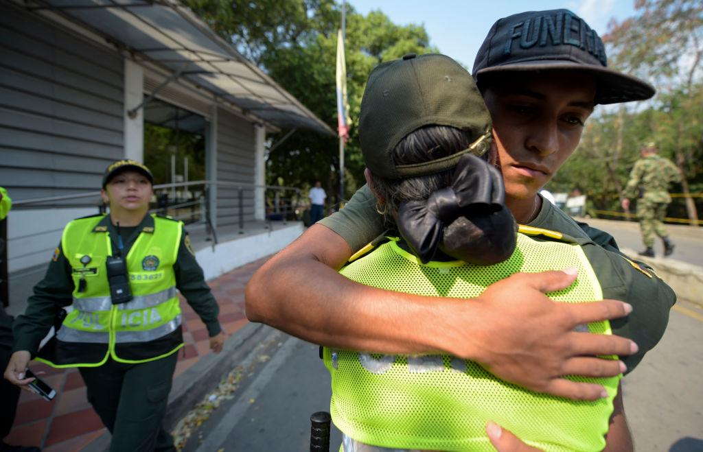Policial colombiana abraça um membro das Forças Armadas da Venezuela (centro) que desertou para a Colômbia, em Cúcuta, em 25 de fevereiro de 2019 (RAUL ARBOLEDA / AFP / Getty Images)