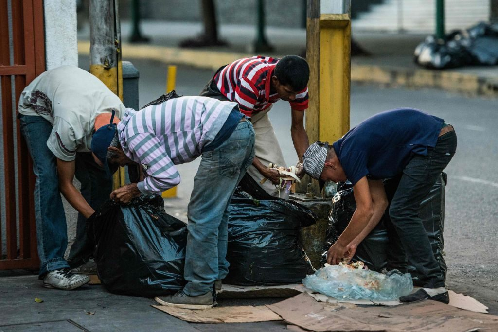 Pessoas procuram comida no lixo nas ruas de Caracas em 22 de fevereiro de 2017 (FEDERICO PARRA / AFP / Getty Images)