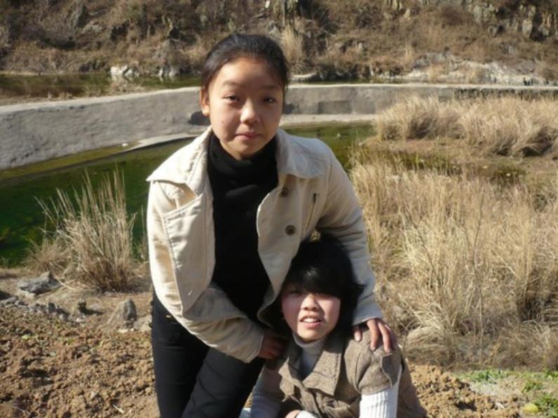 Jiang Liyu (em pé) e sua irmã mais nova a Sra. Jiang Lianjiao (Minghui.org)