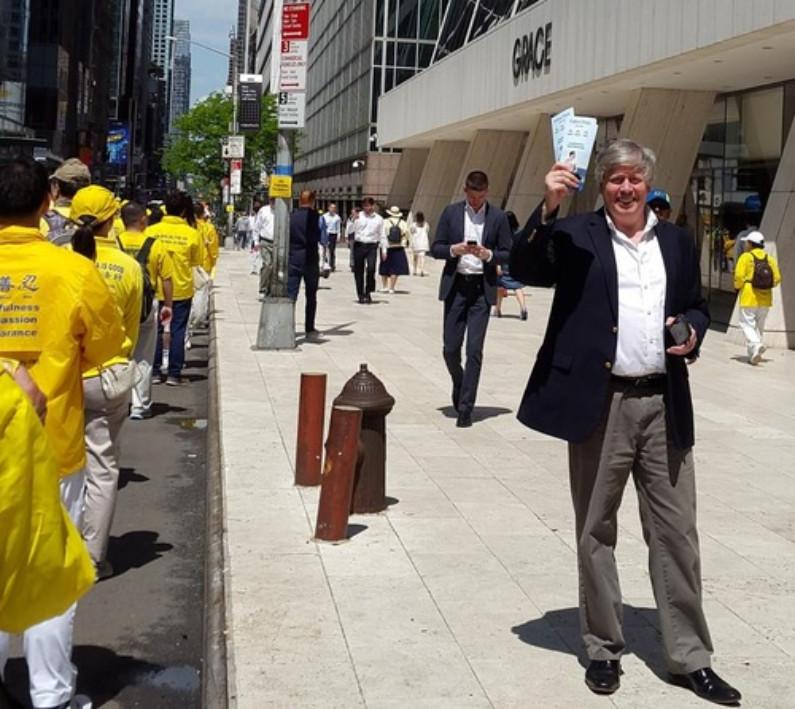 Christopher Leonard disse que muitos de seus colegas que observavam pelas janelas elogiaram o desfile (Minghui.org)