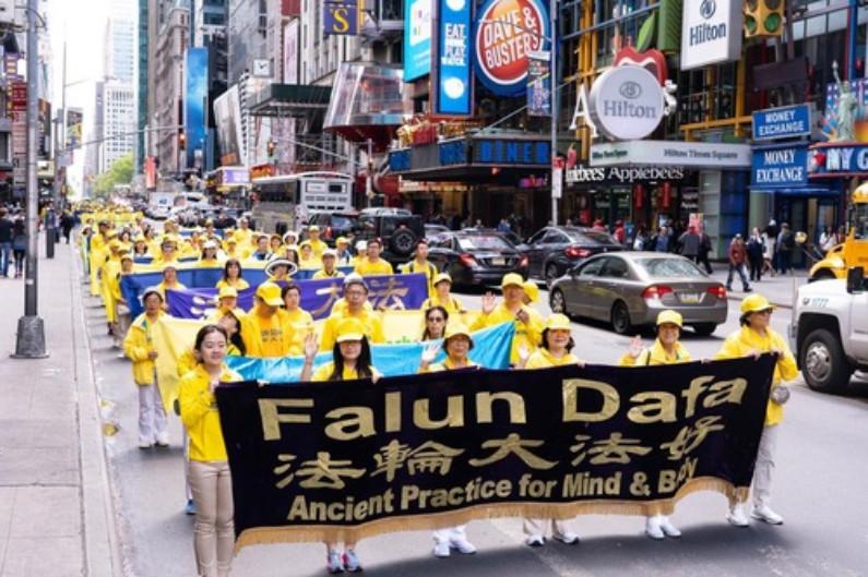 Praticantes carregam banners com várias mensagens (Minghui.org)