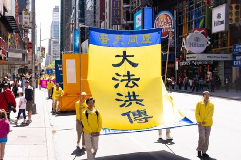 """Banner diz: """"Dafa abraçado em todo lugar, comemoramos juntos"""" (Minghui.org)"""