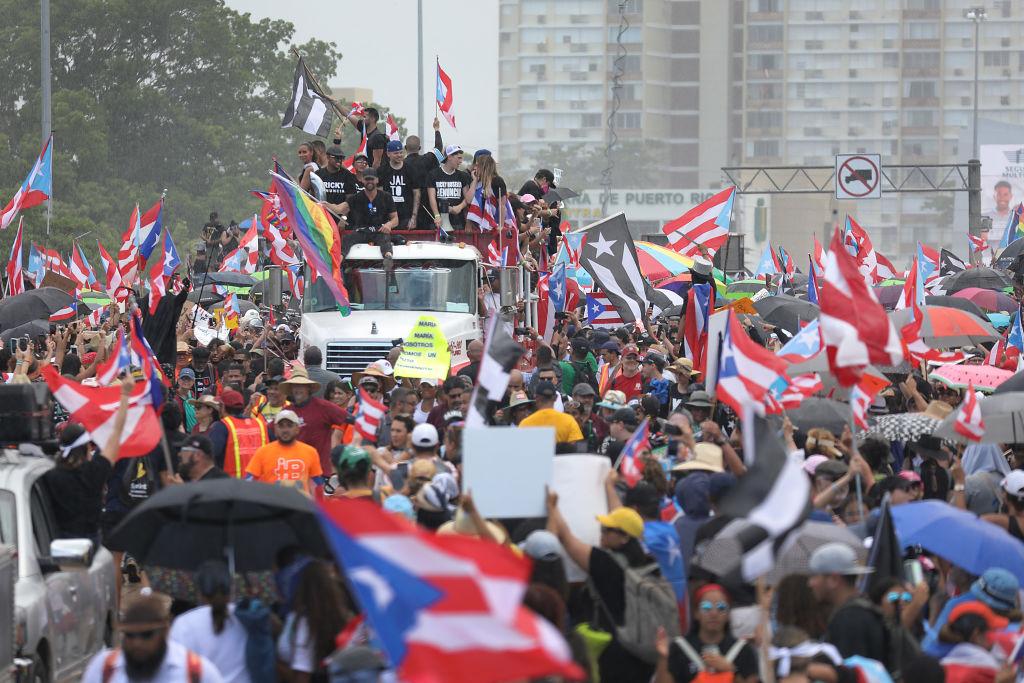 Caminhão transporta o cantor Ricky Martin, o rapper Residente e o rapper Bad Bunny (da esq. para dir.) se juntam a milhares de pessoas que enchem a rodovia Expreso Las Américas para pedir a renúncia do governador Ricardo A. Rosselló em 22 de julho 2019 em San Juan, Porto Rico (Joe Raedle / Getty Images)
