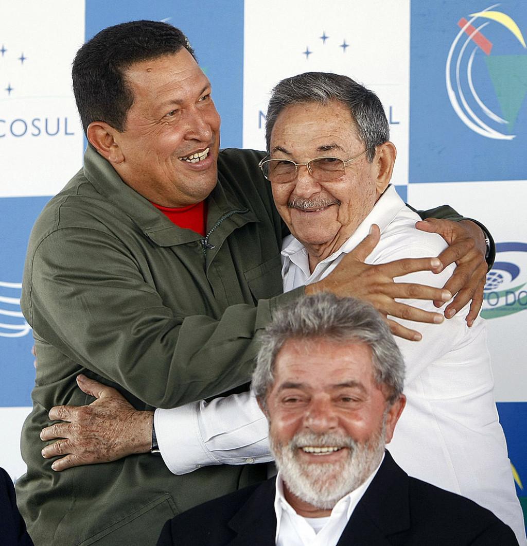 Hugo Chávez (esq.) da Venezuela e Raúl Castro de Cuba se abraçam enquanto o presidente Luiz Inácio Lula da Silva (abaixo) sorri durante a Cúpula do Mercosul, em Sauípe, Brasil, em 16 de dezembro de 2008 (EVARISTO SA / AFP / Getty Images)
