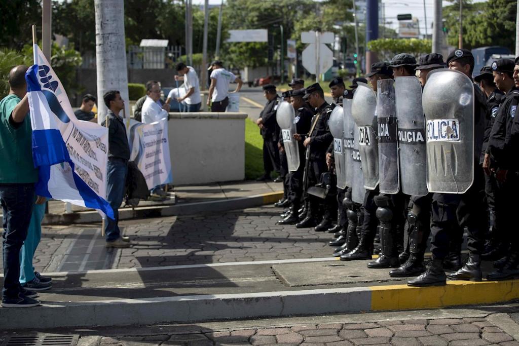 Trabalhadores do setor de saúde protestam na frente do batalhão de choque no sábado (3) em Manágua (Nicarágua). Os trabalhadores exigem que o presidente Daniel Ortega reintegre dezenas de funcionários da saúde demitidos por socorrerem pessoas feridas pelos ataques armados ordenados pelo governo (Jorge Torres/Agência EFE)