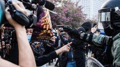 Policial aponta arma para manifestante que segurava cartaz do Epoch Times em Hong Kong