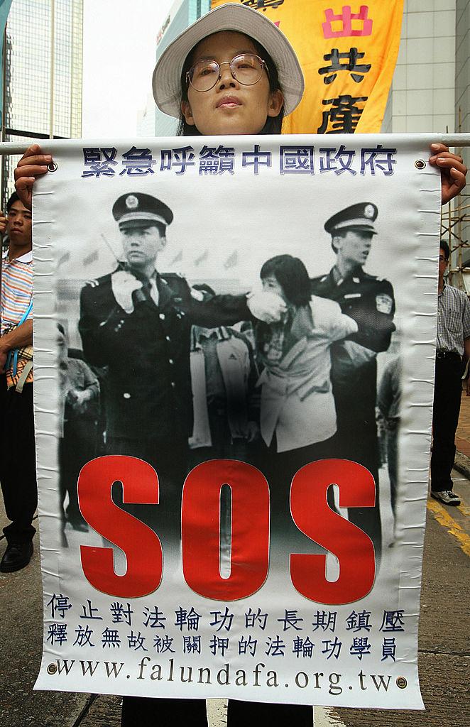 Praticantes do Falun Gong realizam manifestação no distrito central de Hong Kong em 29 de abril de 2006. Centenas saíram às ruas para denunciar a perseguição contra essa prática pacífica levada a cabo pelo regime comunista chinês e para solicitar que sejam investigados os campos de trabalho forçado na China (MIKE CLARKE / AFP / Getty Images)