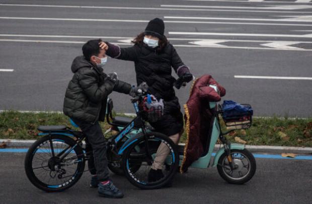 Mulher verifica a temperatura através da testa de seu filho na cidade fechada de Wuhan, na China, em 27 de janeiro de 2020 (Getty Images)