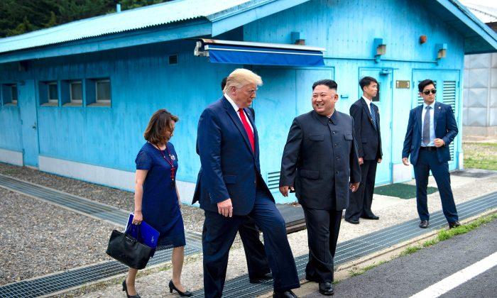 O presidente Donald Trump e o líder norte-coreano Kim Jong Un caminham juntos ao sul da Linha de Demarcação Militar que divide as Coreias do Norte e do Sul em 30 de junho de 2019 (Brendan Smialowski / AFP / Getty Images)