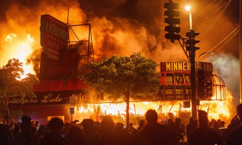 Manifestantes se reúnem em frente a uma loja de bebidas em chamas perto da Terceira Delegacia de Polícia durante um protesto pela morte de George Floyd, um homem negro desarmado, que morreu depois que um policial se ajoelhou em seu pescoço por vários minutos, em 28 de maio de 2020 em Minneapolis, Minnesota, EUA (Keren Yucel/ AFP via Getty Images)