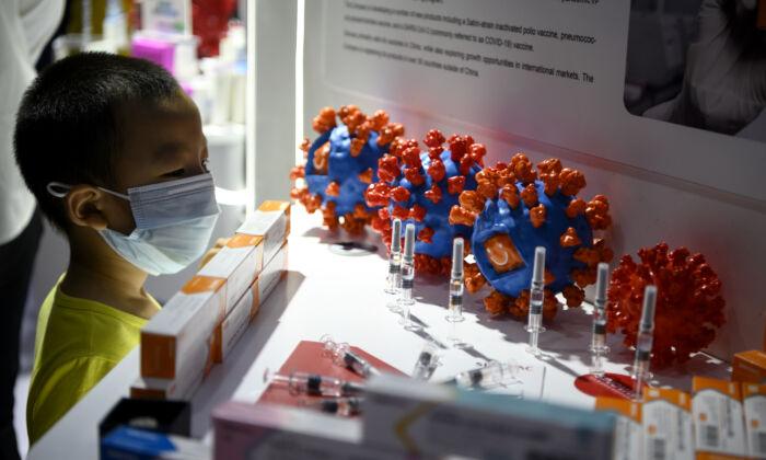 Uma criança observa a vacina candidata Sinovac Biotech LTD para o coronavírus, COVID-19, em exibição na Feira Internacional de Comércio de Serviços da China (CIFTIS) em Pequim, China, em 6 de setembro de 2020 (NOEL CELIS / AFP via Getty Images)