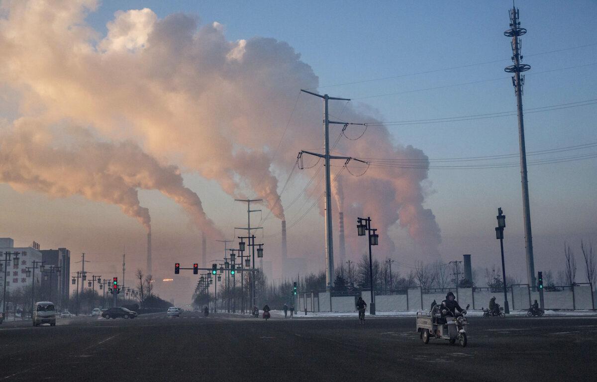 Trabalhadores chineses vão trabalhar enquanto a fumaça sobe de uma usina termoelétrica a carvão em Shanxi, China, em 25 de novembro de 2015 Kevin Frayer / Getty Images)