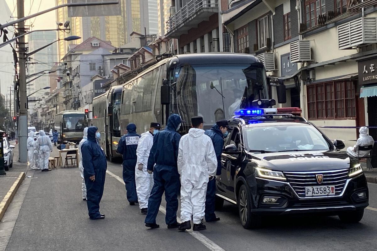 A polícia e os trabalhadores estão ao lado dos ônibus em um bairro onde os residentes são forçados a ir para centros de quarentena centralizados no distrito de Huangpu em Xangai em 21 de janeiro de 2021. (STF / AFP via Getty Imagens)