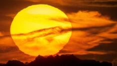 Fotógrafo captura uma visão surreal do enorme pôr do sol por trás de uma formação rochosa icônica no Reino Unido
