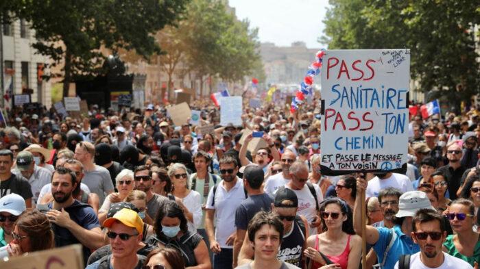 Manifestantes seguram faixas e cartazes durante um protesto nacional contra o covid-19 cartão de saúde da França em 7 de agosto de 2021 em Marselha, França (Roger Anis / Getty Images)