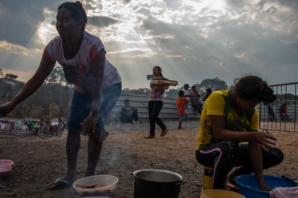 Membros do grupo indígena venezuelano Warao preparam comida no abrigo da ONU Janokoida em 6 de abril de 2019 em Pacaraima, Brasil. Mais de 900 pombos indígenas foram deslocados para o Brasil como resultado do medo, da ameaça que eles têm (Victor Moriyama / Getty Images)