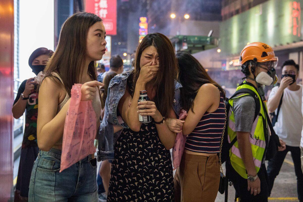 Pedestres reagem depois que a polícia disparou gás lacrimogêneo para dispersar manifestantes pró-democracia no distrito de Mong Kok, em Hong Kong, em 27 de outubro de 2019 (Dale De La Rey / AFP via Getty Images)