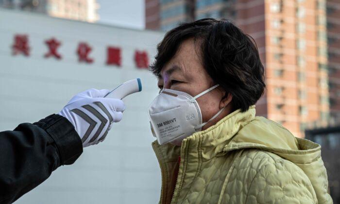 Um guarda de segurança verifica a temperatura de uma mulher usando uma máscara protetora na entrada de um parque em Pequim, China, em 31 de janeiro de 2020 (NICOLAS ASFOURI / AFP via Getty Images)