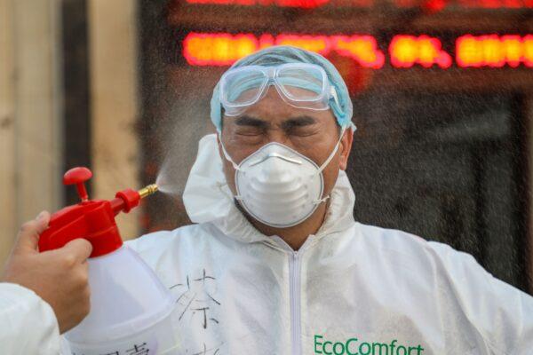 Um médico é desinfetado por seu colega em um hospital em Wuhan, China, em 3 de fevereiro de 2020 (STR / AFP via Getty Images)
