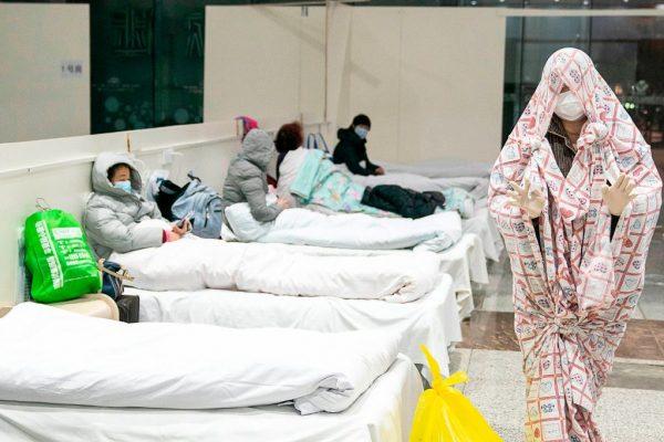 Um paciente é coberto com um cobertor em um centro de exposições transformado em hospital quando começa a aceitar pacientes com sintomas do novo coronavírus em Wuhan, na província central de Hubei, na China, em 5 de fevereiro de 2020 (STR / AFP via Getty Images)