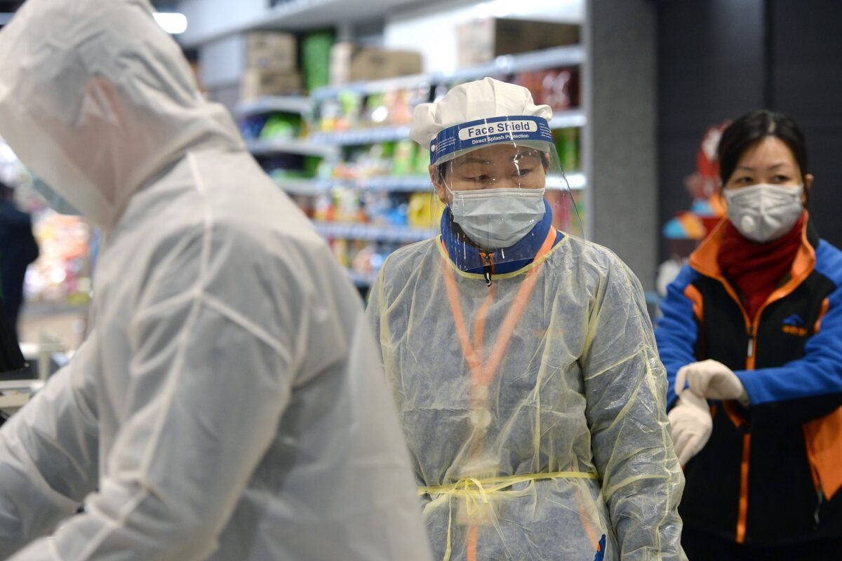 Um membro da equipe que usa máscara e traje de proteção trabalha em um supermercado em Wuhan, o epicentro do surto de um novo coronavírus, na província central de Hubei, na China, em 10 de fevereiro (STR / AFP via Getty Images)